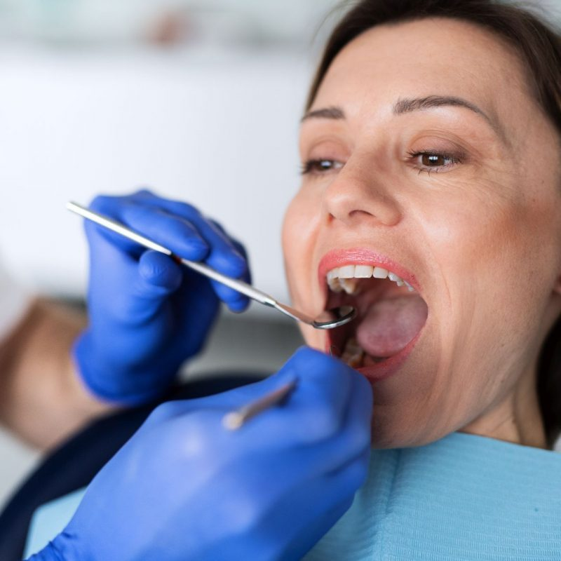 A woman has an annual dental check-up in dentist surgery.